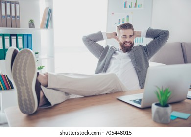 Happy satisfied businessman watching video on his laptop while having a break at work place, hands behind the head and feet on the desktop