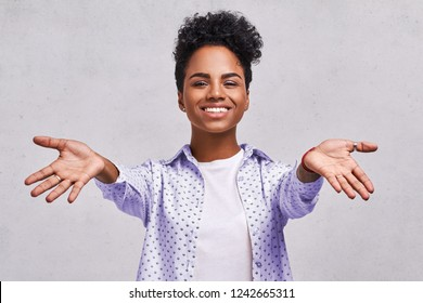 Happy satisfied dark skinned girl gives hug at camera, spreads hands, meets with close friend, dressed casually, isolated over white background. Come to me, I want to embrace you. Pleasant feelings.