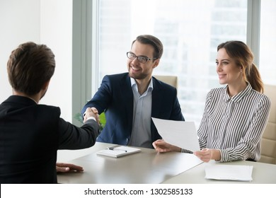 Happy satisfied hr manager handshaking hiring successful male job candidate, smiling employer company executive shaking hand welcoming greeting seeker making good first impression, employment concept