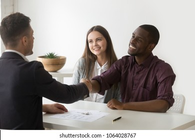 Happy satisfied interracial couple and realtor shaking hands making real estate deal, smiling african customer handshaking agent signing family mortgage loan investment contract for buying new house