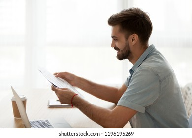 Happy satisfied millennial man sitting at the desk holding letter paper about recruited hired on a good post. Student reading pleasant news about scholarship or examination test passed successfully
