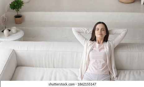 Happy satisfied millennial woman owner renter of new apartment. Female having rest sitting in comfortable pose on sofa at living room with modern interior design, copy space.