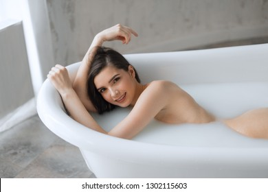 Happy satisfied naked girl with long wet brown hair smiles at camera while enjoying a bath with milk and hot steaming water. Spa body care.