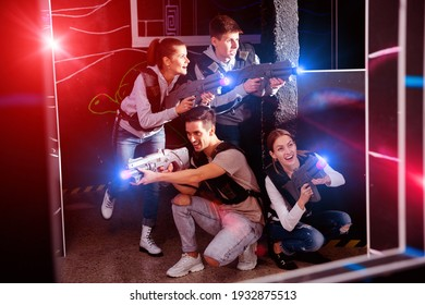 Happy satisfied pleasant smiling young people with laser pistols posing together on dark laser tag labyrinth.