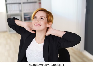 Happy satisfied young businesswoman relaxing stretching her back with her hands behind her head and looking upwards with a smile