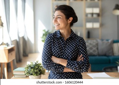 Happy satisfied young indian woman student teacher freelancer look away dream about good future vision, smiling pretty girl professional stand arms crossed at home hope for new opportunities concept