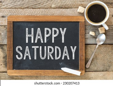 Happy Saturday sign on Blackboard. Blackboard with Happy Saturday sign and cup of coffee on wooden background