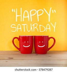 Happy saturday word. Two cups of coffee and stand together to be heart shape on yellow background with smile face on cup.