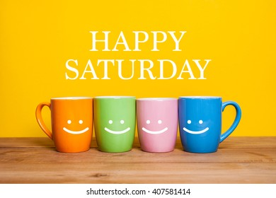 Happy saturday word.cups of coffee and stand together on yellow background with smile face on cup.