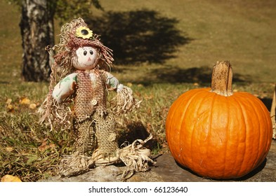 A happy scarecrow with pumpkin.