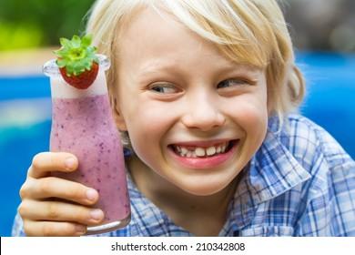 Happy school boy drinking a healthy smoothie as a snack