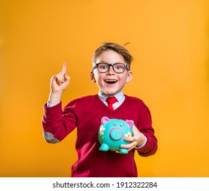 Happy school boy with money pointing up isolated on yellow. Cool stylish businessman. How to be rich. Portrait of a cute nerdy boy carrying a piggy bank with his savings. Success, motivation, winner.