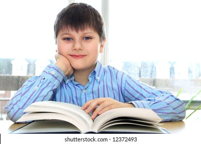 Happy school boy studying with a book