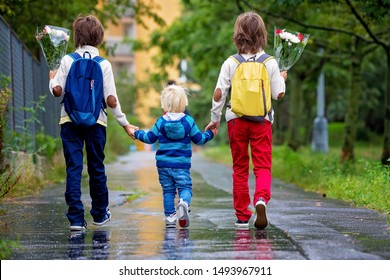 Happy school children, holding bouquet of flowers, going to school first day, rainy autumn day in september
