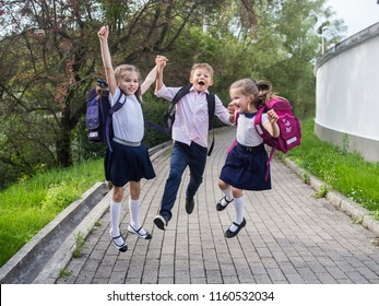 Happy school children in uniform and with backpacks holding hands and jumping in the park, back to school and September 1 concept