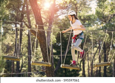 Happy school girl enjoying activity in a climbing adventure park on a summer day