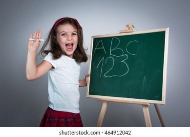 Happy School Girl in front of the Green Chalk Board