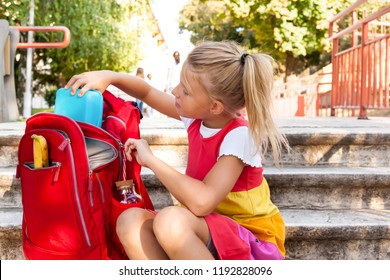 Happy school girl pull out lunchbox from her backpack in the schoolyard - lunch break