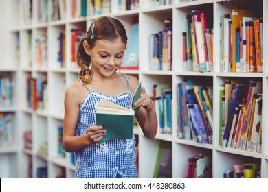Happy school girl reading a book in library at school