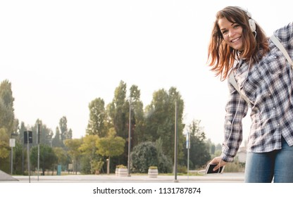 happy school girl with smartphone and headset going to college and listening to digital music. campus park on background. education, teenagers, rock music and positive attitude concept.