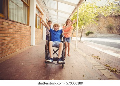 Happy school kids pushing a boy on wheelchair in school corridor