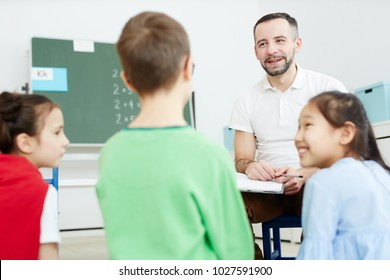 Happy school teacher or psychologist and two girls listening to schoolboy idea