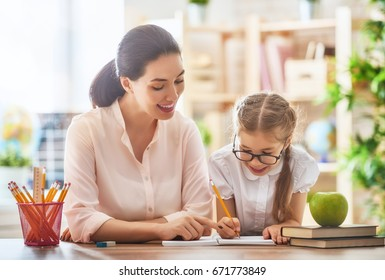 Happy school time. Mother and daughter are learning to write. Adult woman teaches child the alphabet.