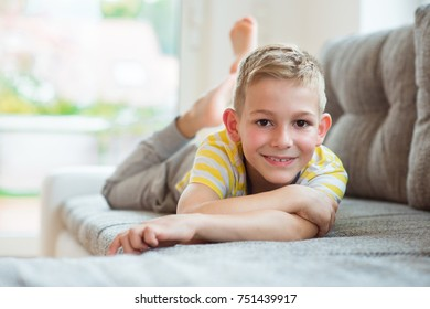 Happy schoolboy 9 years old lying on sofa at home