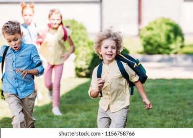 happy schoolboy with classmates runing by school garden
