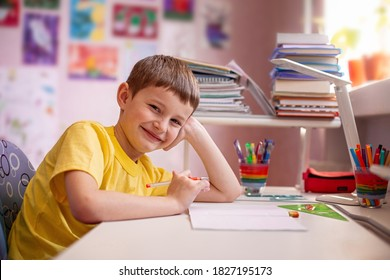 Happy schoolboy doing homework with training books and notebooks at home in your room. Learning at home. Distance learning.
