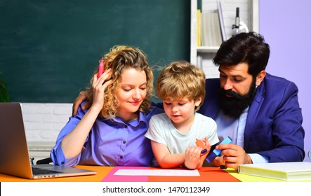 Happy schoolboy at lesson. Cute pupil and his father and mother in classroom. School education. September 1. Ready to study. Beginning of lessons. Child from elementary school with parents in school.