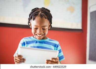 Happy schoolboy using digital tablet in classroom at school