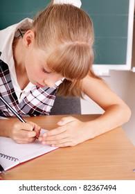 Happy schoolchild near blackboard.