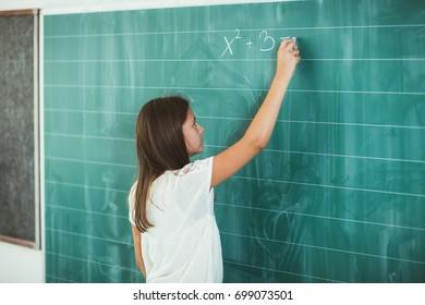 Happy schoolchild writing on blackboard