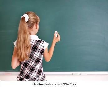 Happy schoolchild writing on blackboard.