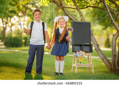 Happy schoolchildren with backpacks outdoors