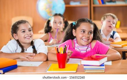 Happy schoolchildren during lesson in classroom at school