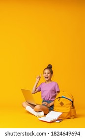happy schoolgirl with backpack, laptop and books is sitting on yellow background in the Studio. The child shows, a sign of approval, a finger up. Back to school. copy space.