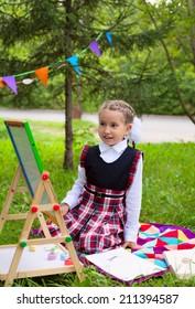 Happy schoolgirl child kid girl sitting on grass and writing on chalkboard, classroom outdoors, celebration