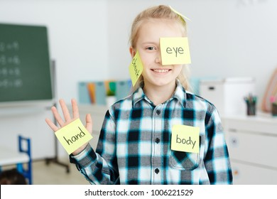 Happy schoolgirl having sticky notepapers with English names of body parts on her hand, cheek and eye