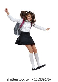 Happy schoolgirl jumping  in a  studio against white background