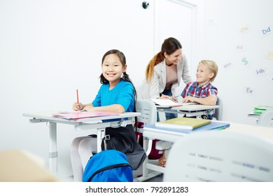 Happy schoolgirl looking at camera by desk with her teacher and classmate talking on background