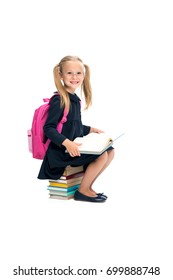 happy schoolgirl sitting on stack of books isolated on white