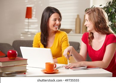 Happy schoolgirls laughing at each other sitting at table at home with laptop and books.