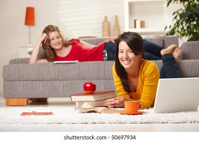 Happy schoolgirls learning at home in living room with books and laptop, looking at camera smiling.