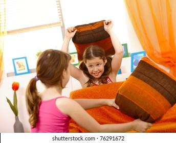 Happy schoolgirls in pillow fight in living room.?
