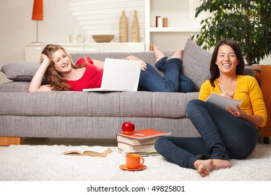 Happy schoolgirls studying together in living room with books and computer, laughing.
