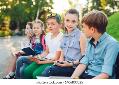 Happy Schoolmates Portrait. Schoolmates seating with books in a wooden bench in a city park and studying on sunny day