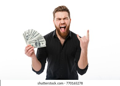 Happy screaming bearded business man in shirt holding money and showing rock gesture while looking at the camera over white background
