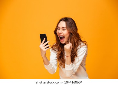 Happy screaming brunette woman in sweater holding smartphone and rejoices over yellow background